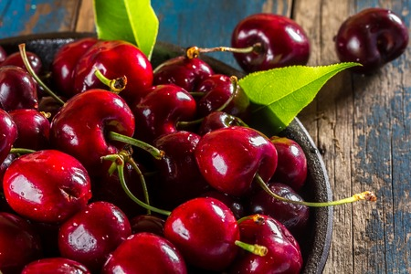 Fresh cherry on black plate on wooden background. Close up Stock Photo