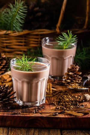 Traditional chilean alcohol Christmas drink Cola de mono - momkey tail with milk, aguardiente, cofee and spices on wooden board decorated fir tree brunches