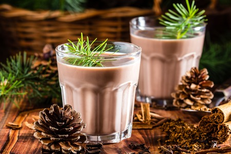 chilean: Traditional chilean alcohol Christmas drink Cola de mono - momkey tail with milk, aguardiente, cofee and spices on wooden board decorated fir tree brunches