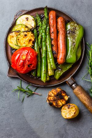グリーン野菜のグリル - ズッキーニ、アスパラガス、ピーマン、ニンニク、ソーセージ、レモン、ローズマリー鋳鉄のグリルパンします。スレート  写真素材