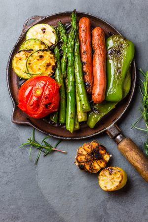 Grilled green vegetables - zucchini, asparagus, bell pepper, garlic, sausages, lemon and rosemary on cast iron grill pan. Gray slate background. Top view Standard-Bild