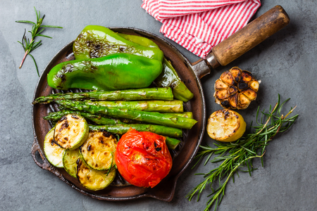 Grilled green vegetables - zucchini, asparagus, bell pepper, garlic, sausages, lemon and rosemary on cast iron grill pan. Gray slate background. Top view Stock Photo