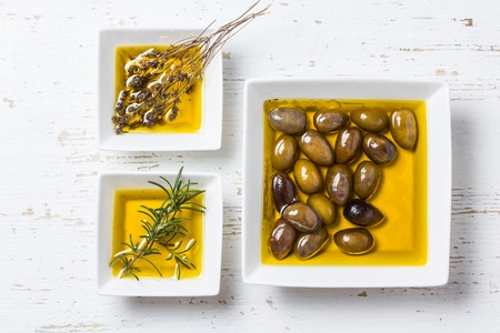 additional: Olive oil with fresh herbs on white background. Stock Photo