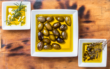 Olive oil with fresh herbs on white background. Stock Photo