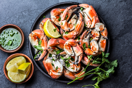 Crabs tentacles with wite wine, lemon, herbs sauce, slate background Stock Photo
