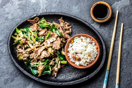 Traditional chinese mongolian beef stir fry on iron plate with rice and soya sauce on slate background. Top view, copy space Standard-Bild