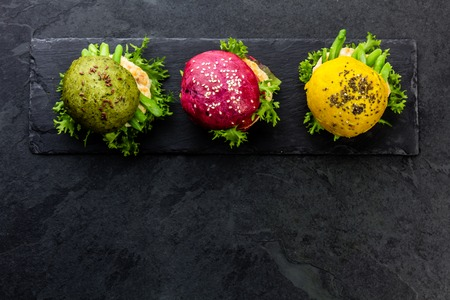 linseed: Colored green, yellow and purple burgers on slate board. Top view