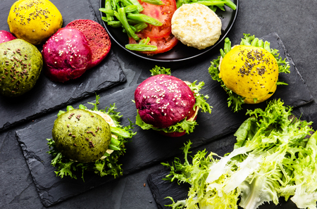 colorfull: Colored green, yellow and purple burgers on slate board. Top view