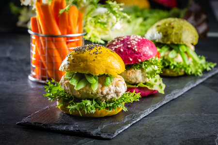 colorfull: Colored green, yellow and purple burgers on slate board, slate background