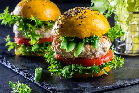 colorfull: Colored yellow burgers. Homemade American chicken burgers hamburgers with turmeric curcuma and chia buns and vegetables. Trendy food. Close up, slate background.