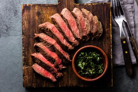 Fette di manzo medio di bistecca rara su tavola di legno, bicchiere di vino rosso su sfondo ardesia Archivio Fotografico - 81361246