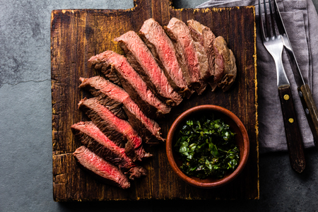 Slices of beef medium rare steak on wooden board, glass of red wine on slate background Stockfoto