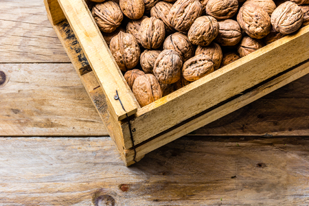 Box of walnuts on wooden background. Harvest concept
