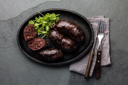 Blutige Würste - chilenische Preta auf schwarzem Eisenplatte, Draufsicht, grauer Schieferhintergrund