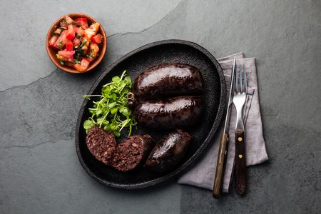 Blutige Würste - chilenische Preta auf schwarzem Eisenplatte, Draufsicht, grauer Schieferhintergrund Standard-Bild