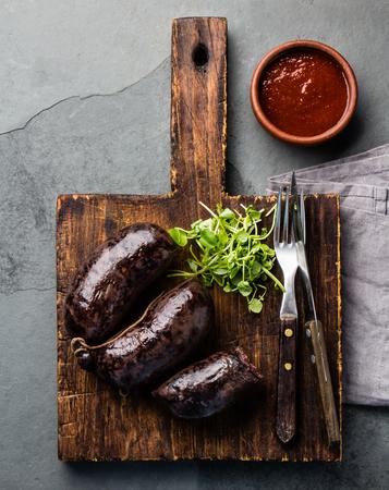 Blutige Würstchen - Prieta auf Holzbrett mit Chili-Sauce, Schieferhintergrund