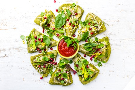 Green spinach dough, vegetables and cheese pizza on wite background