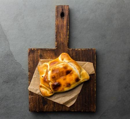 Chilean empanada de pino on wooden board