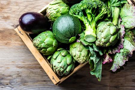 Koken achtergrond oogst concept. Verse biologische groene groenten in houten kist