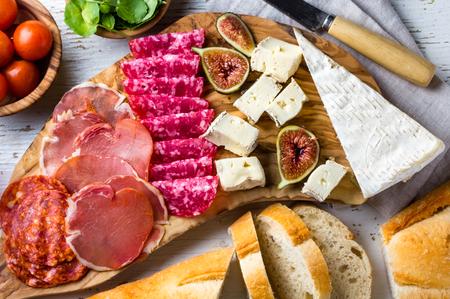 Antipasto olive wood board with salami, ham serrano, cheese, nuts and ciabatta bread
