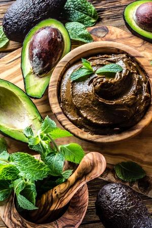 オリーブの木のボウルにアボカド チョコレートのムース。木の暗 写真素材