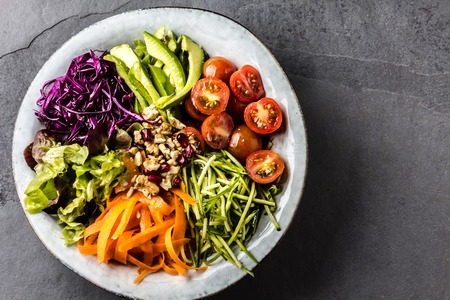 Buddha bowl. Vegetables nuts salad on slate background