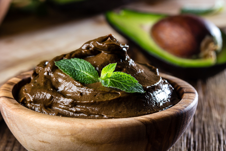 Avocado chocolate mousse in olive wooden bowl. Wooden bacground