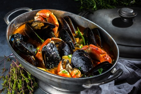 Seafood mussels crabs soup in metal pot, gray background
