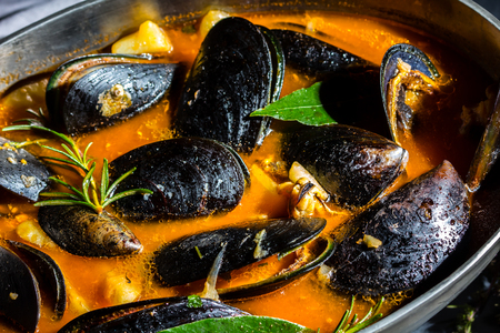 Seafood mussels tomato soup in metal pot, gray background
