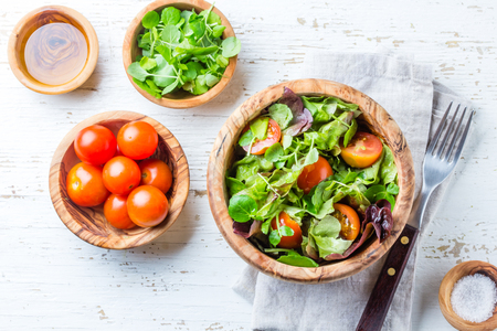 berro: Vegetarian salad with lettuce and tomatoes in olive wooden bowl on wihte background Foto de archivo