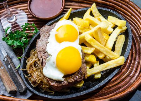 Comida latinoamericana peruana. Lomo a lo pobre. Carne de vaca frita con papas fritas y huevo francés servido con salsa de chile y vino Foto de archivo - 81659350