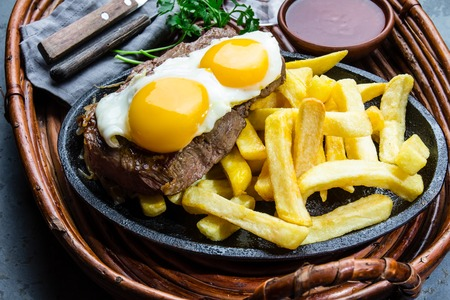 Peruvian Latin American food. Lomo a lo pobre. Beef whit fried potatoes french fry and egg served with chile sauce and wine