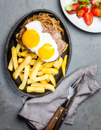 Peruvian Latin American food. Lomo a lo pobre. Beef whit fried potatoes french fry and eggs Stock Photo
