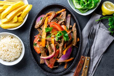 ペルー料理のロモ saltado - 紫玉ねぎ、黄色の唐辛子、トマトと牛フィレ肉は、フライド ポテトとライスと黒のプレートで楽しめます。トップ ビュー