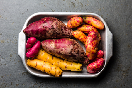 plant sweet: Peruvian raw ingredients for cooking - yuca, colored sweet potatoes and camote batata. Top view.