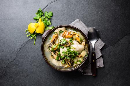 粘土の鉢海鮮魚のスープ コリアンダーとレモンを添えてください。上面図、空間をコピーします。