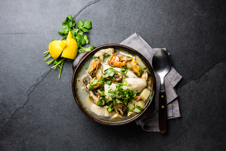 Seafood fish soup in clay bowls served with lemon and coriander. Top view, copy space. Standard-Bild