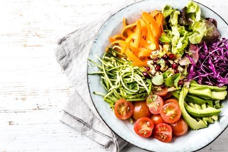 鉢の石仏。白い背景の上の野菜のナッツのサラダ