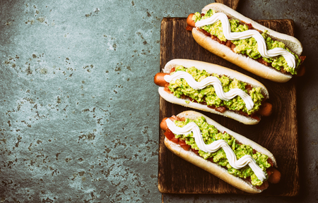 Chilean Completo Italiano. Hot dog sandwiches with tomato, avocado and mayonnaise on wooden board. Top view, copy space