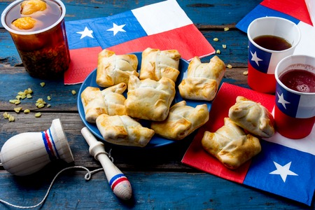 Chilean independence day concept. fiestas patrias. Chilean typical dish and drink on independence day party, 18 september. Mini empanadas, mote con huesillo, wine with toasted flour, chicha and tipical play emboque Standard-Bild