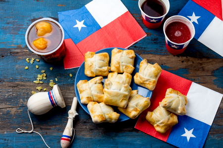 Chilean independence day concept. fiestas patrias. Chilean typical dish and drink on independence day party, 18 september. Mini empanadas, mote con huesillo, wine with toasted flour, chicha and tipical play emboque Foto de archivo