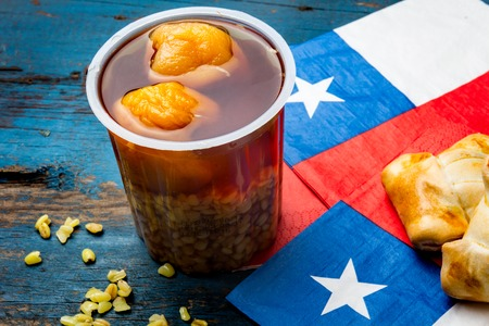 Chilean independence day concept. fiestas patrias. Chilean typical dish and drink on independence day party, 18 september. Mini empanadas, mote con huesillo, wine with toasted flor, chicha and tipical play emboque Stock Photo - 84704061