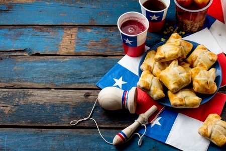 Chilean independence day concept. fiestas patrias. Chilean typical dish and drink on independence day party, 18 september. Mini empanadas, mote con huesillo, wine with toasted flour, chicha and tipical play emboque Archivio Fotografico