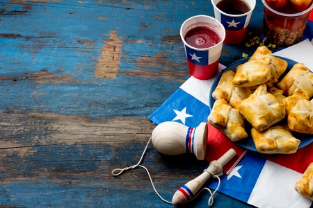 Chilean independence day concept. fiestas patrias. Chilean typical dish and drink on independence day party, 18 september. Mini empanadas, mote con huesillo, wine with toasted flour, chicha and tipical play emboque Banco de Imagens