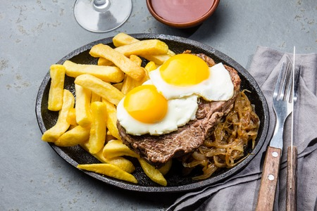 Peruvian Latin American food. Lomo a lo pobre. Beef tenderloin whit fried potatoes french fries and eggs Stock Photo