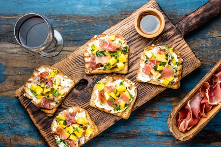 Toasts with cream cheese, ham jamon serrano and mango served on wooden board with red wine, blue wooden rustic background, top view