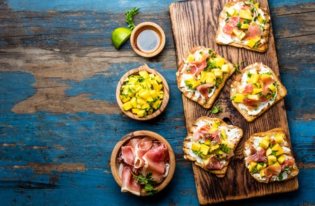 peppercorn: Toasts with cream cheese, ham jamon serrano and mango served on wooden board with red wine, blue wooden rustic background, top view, copy space