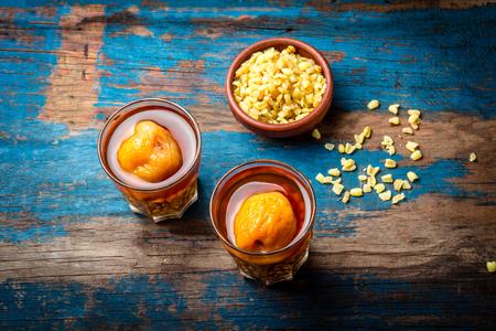 モテ con huesillo。作られた伝統的なチリ飲料玄米小麦を料理、木の板、素朴な青色の背景に桃を乾燥しました。