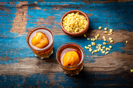 Mote con huesillo. Traditional Chilean drink made from cooked husked wheat and dried peach on wooden board, rustic blue background