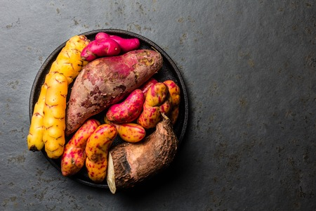 Peruvian raw ingredients for cooking - yuca, colored sweet potatoes and camote batata. Top view.
